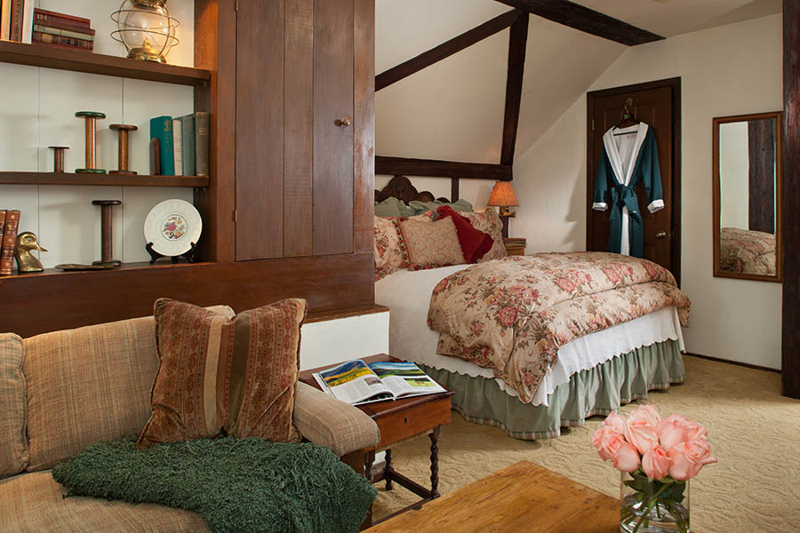 dovecote room with bed, sitting area and fireplace