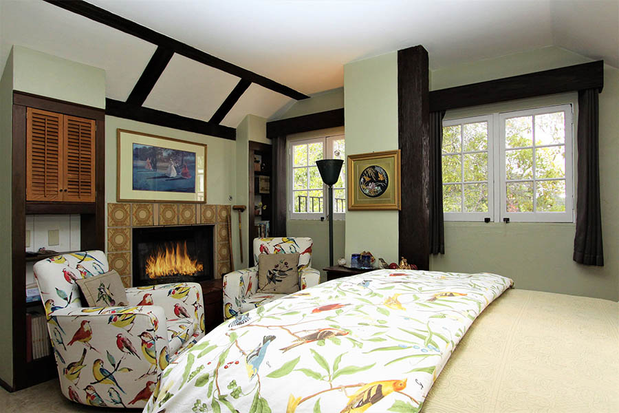 rookery room with fireplace and bird motif on bed and chairs
