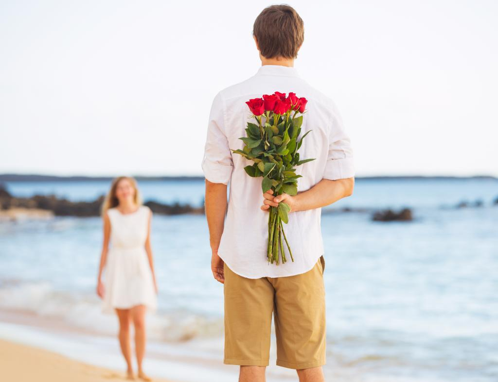 couple at beach with flowers behind his back