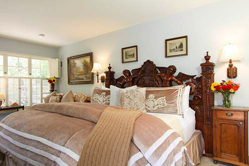 luxury guest room with bed and wood carved headboard