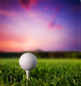 Golf ball on tee. Green grass, sunset.