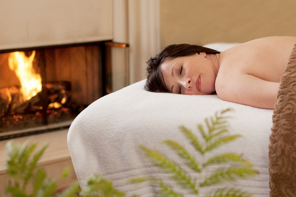 Woman on Spa Table by Fireplace